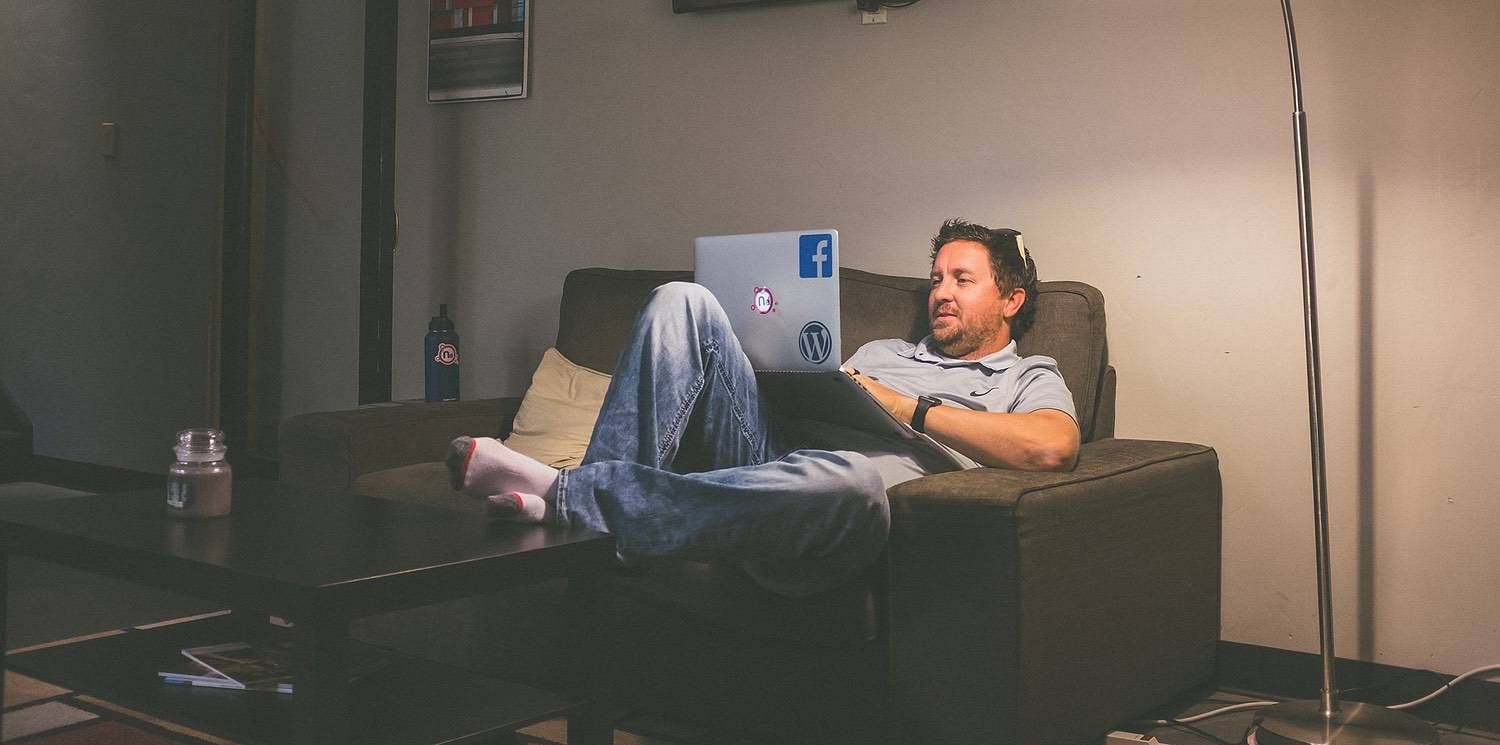 A man sitting on a couch with his laptop